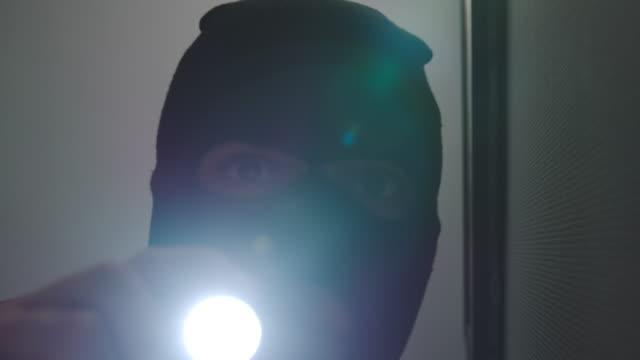 vídeos de stock e filmes b-roll de thief shines a flashlight into a surveillance camera - lanterna elétrica