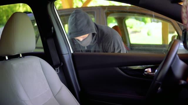 vídeos de stock e filmes b-roll de thief steals car at parking - ladrão