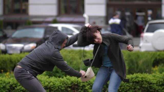 vídeos de stock, filmes e b-roll de ladrão que tenta roubar a bolsa da mulher no parque da cidade - autodefesa