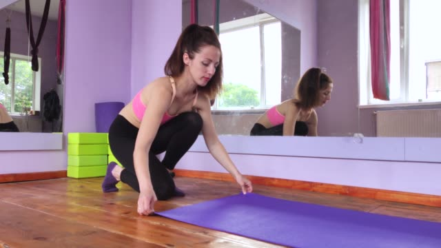 A thin and fit woman spreads a mat for sports, fitness or yoga. Bright room with wooden floors and mirrors