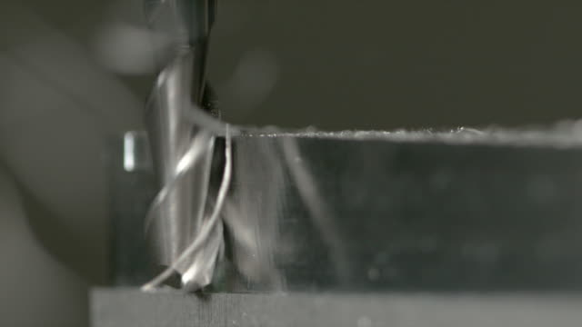 makro, dof: tunna bitar av metall flyga bort ett block av aluminium under svarvning - cnc maskin bildbanksvideor och videomaterial från bakom kulisserna