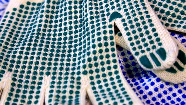 Thin work gloves with blue and green pimples on a rotating surface, Personal protective equipment background.
