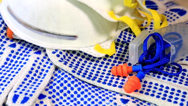 Thin work gloves with blue pimples, protective glasses, respirators and ear plugs on a rotating surface, Personal