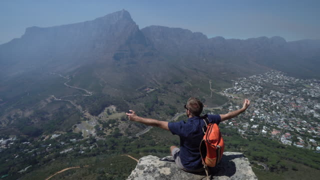 thing on rock, arms outstretched Young man hiker sitting on rock on top of Lion's Head cape peninsula stock videos & royalty-free footage