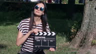 istock Thin-haired girl with clapboard in the park 1318439489