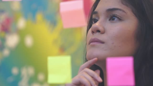 thinking about ideas and strategy in studio office - post it video stock e b–roll