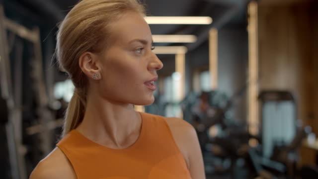 stockvideo's en b-roll-footage met denkende atleetvrouw die smartphone bij gymnastiek gebruikt. het meisje dat van de sport in sportclub sms't - call center
