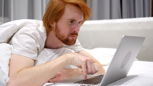Thinking Redhead Beard Man Working on Laptop Lying in Bed video