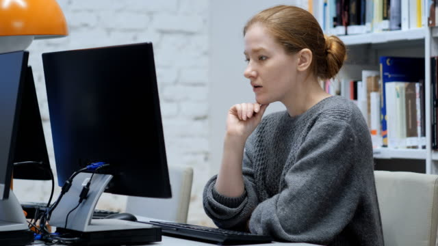 Thinking Redhead Woman Working on Laptop, Sitting In Office video