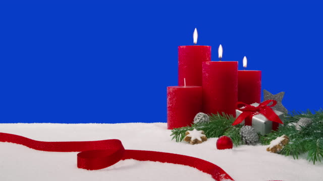 Third Sunday of Advent - Christmas decoration arrangement on a snowy table in front of a blue screen. A Christmas decoration arrangement with four candles, fir branches, a wrapped gift, scattered decoration elements and a red ribbon on a snowy table in front of a blue screen. Three candles are lit, which are burning with beautiful flames. weihnachten stock videos & royalty-free footage