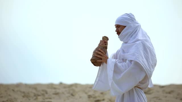 acqua potabile pellegrina araba assetata dalla bottiglia nel deserto, problemi di siccità - cultura del medio oriente video stock e b–roll
