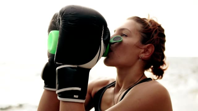 thirsty female boxer in gloves taking a break drinking from the water bottle after training. beautiful woman training by the sea - runner rehab gym video stock e b–roll
