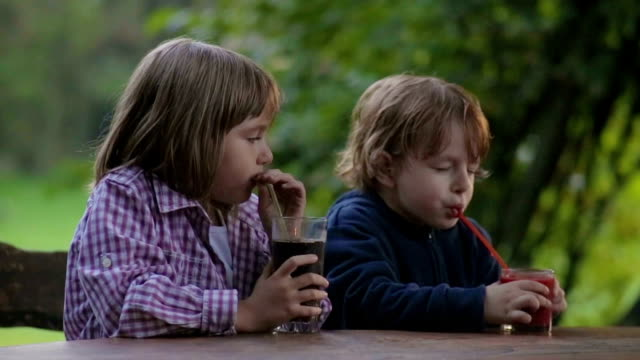 Thirsty Girl and boy drinking juice Outdoors video
