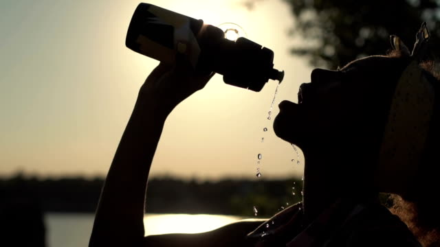 Thirsty girl drinking water while trekking Slow motion shot side view of silhouette African young girl drinking water and pouring herself in summer heat while traveling. thirsty stock videos & royalty-free footage