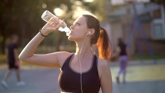 vidéos et rushes de femme de soif sport prenant une pause avec le verre de la bouteille d'eau en dehors de repos - canicule