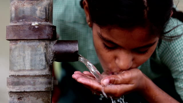 Thirsty HD1080p: Teenager girl of Indian ethnicity wearing school uniform drinking water outdoor in the nature. purified water stock videos & royalty-free footage