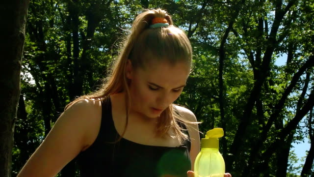 Thirsty woman open sport bottle with water. Tired woman holding plastic bottle Thirsty woman open sport bottle with water. Tired woman holding plastic bottle with cold water in hand. Closeup of fitness woman resting after running outdoor at summer. thirsty stock videos & royalty-free footage