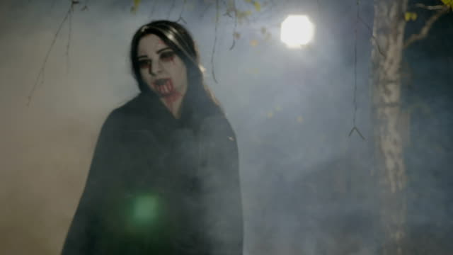 Thirsty young female vampire coming out from forest to hunt and showing her teeth on halloween night video