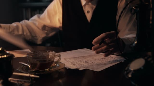 thirties businessman closeup writing 4k Close up scene of the hands of a 1930s businessman with fountain pen making entries into a ledger. sepia toned stock videos & royalty-free footage