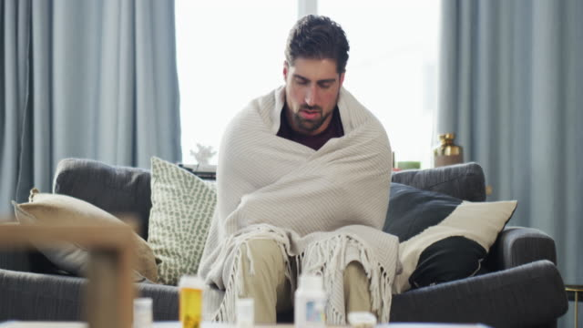 This has to be the worst fever I've ever had 4k video footage of a handsome young man shivering with a fever while wrapped up in a blanket on the sofa at home flu stock videos & royalty-free footage
