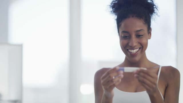 This is the best news ever! 4k video footage of a young woman looking happy after taking a pregnancy test at home good news stock videos & royalty-free footage