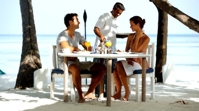 This is the life Young couple having lunch on a tropical beach in front of the oceanhttp://195.154.178.81/DATA/i_collage/pi/shoots/779829.jpg tourist resort stock videos & royalty-free footage