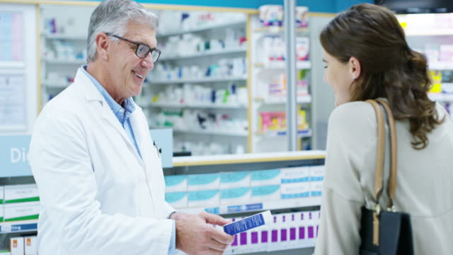 This is what you need 4k video footage of a handsome senior male pharmacist helping a young woman in the pharmacy pharmacist stock videos & royalty-free footage