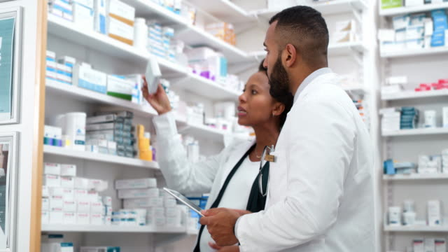 This looks like the one... 4k video footage of two pharmacists working on a tablet together in a chemist lab coat stock videos & royalty-free footage