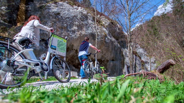 den medelålders mannen driver en cykel upp på en kulle eftersom han vill rick så kallade resten punkt där han kommer att ha en vacker utsikt över den gröna dalen. - endast flickor bildbanksvideor och videomaterial från bakom kulisserna