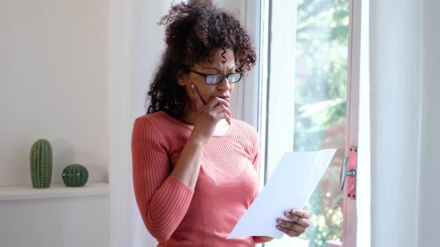dieses video handelt von einer schwarzen amerikanerin, die ein dokument liest - haushaltskosten stock-videos und b-roll-filmmaterial