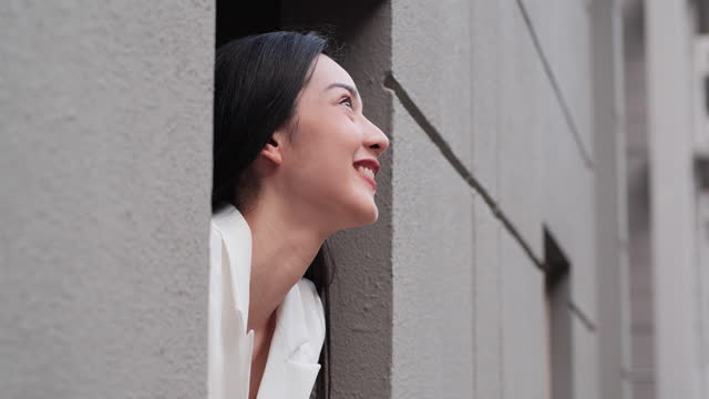 A thoughtful attractive Asian woman looking outside from her room and smiling.