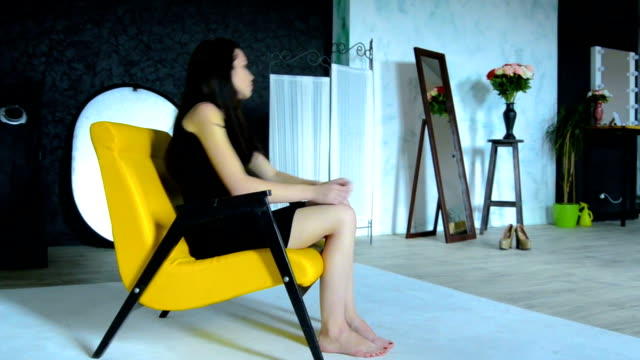 thoughtful attractive brunette in black dress sitting on a Chair video
