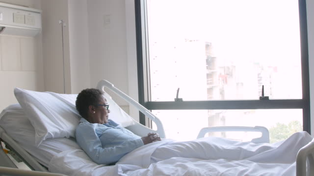 Thoughtful black female patient looking away to window while lying down on hospital bed Thoughtful black female patient looking away to window while lying down on hospital bed - Healthcare hospital bed stock videos & royalty-free footage