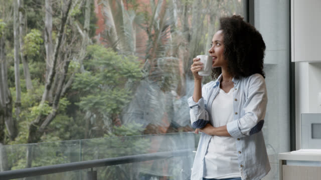 Thoughtful black young woman enjoying a hot chocolate and looking at window view very relaxed
