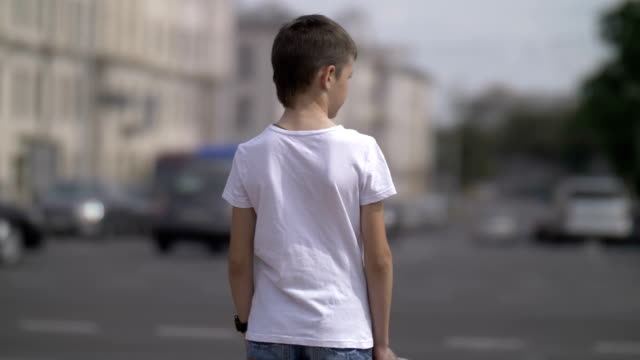 thoughtful boy stands near traffic of cars, caution