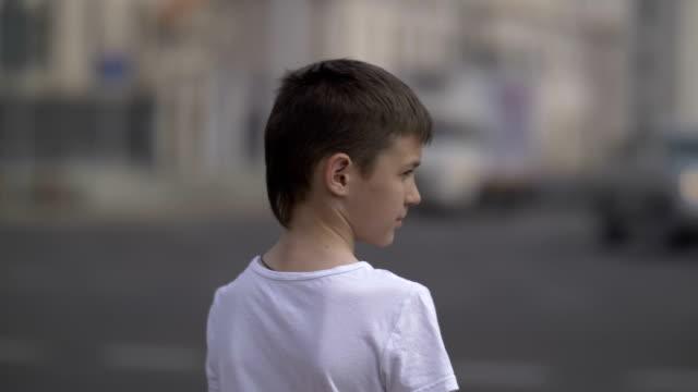 stockvideo's en b-roll-footage met nadenkende jongen staat in de buurt van verkeer van auto's, voorzichtigheid - oversteekplaats