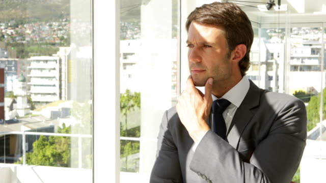 Thoughtful businessman looking out window video