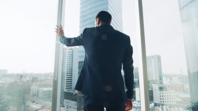 vídeos de stock, filmes e b-roll de pensativo empresário vestindo terno de pé em seu escritório, olhando para fora da janela e contemplando o próximo contrato de grandes negócios. major cidade empresarial, com vista panorâmica da janela. cores azuis. - ceo