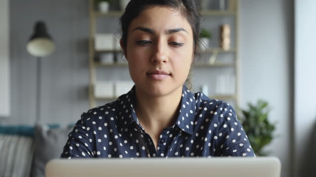 Thoughtful concerned indian woman working on computer thinking solving problem