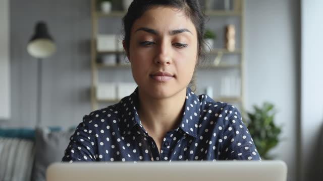 vídeos de stock, filmes e b-roll de mulher indiana preocupada pensativa trabalhando em computador pensando resolver problema - contemplação