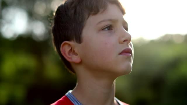 希望と信仰を持って空を見上げる思慮深い熟考の子供。ペンシブ少年 - 希望点の映像素材/bロール