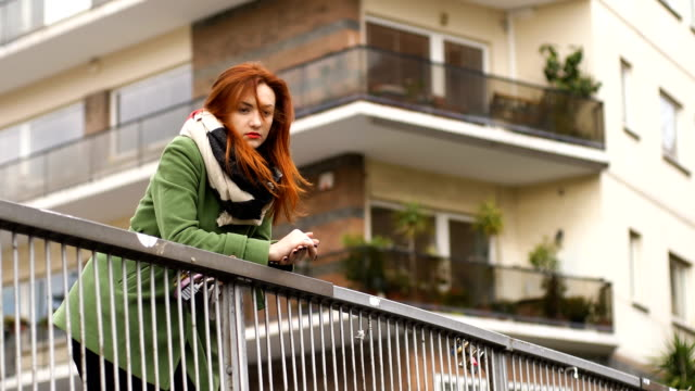 thoughtful day dreaming beautiful woman looking out over the balustrade - balaustrata video stock e b–roll