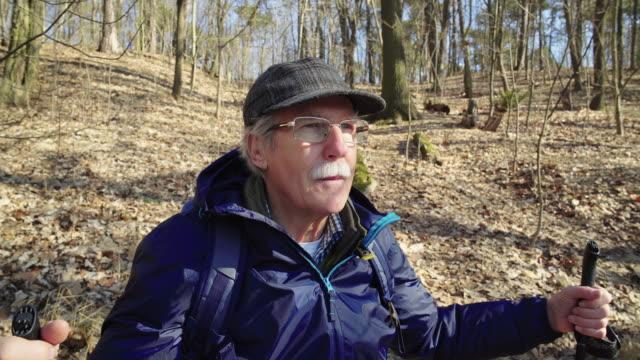 escursionista anziano premuroso che cammina nella foresta - distrarre lo sguardo video stock e b–roll