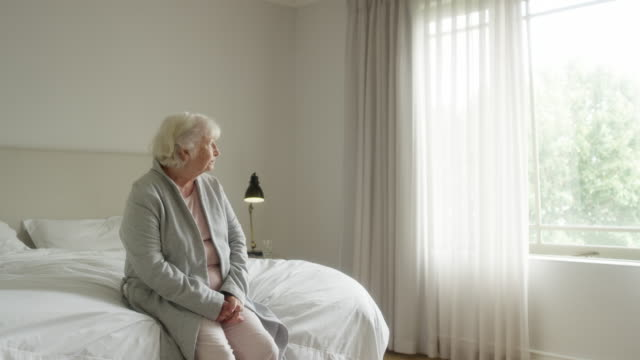 Thoughtful elderly woman sitting on bed