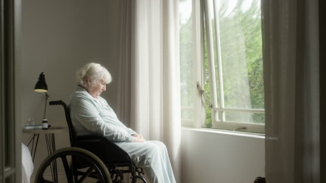 Thoughtful elderly woman sitting on wheelchair Thoughtful senior woman sitting on wheelchair at home. Elderly female is looking through window. She is in bedroom. wheelchair stock videos & royalty-free footage