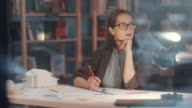 istock Thoughtful Female Architect Working on Floor Plan at Desk in Office 1252399355