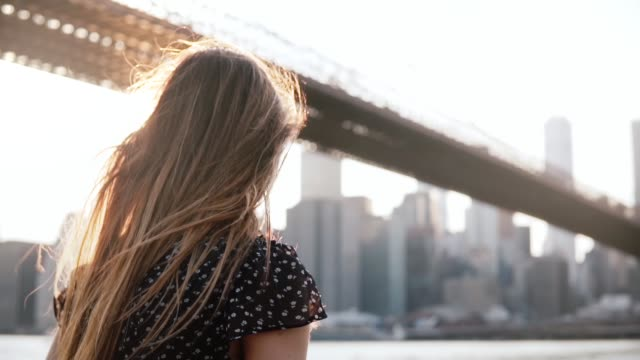Thoughtful girl in sunglasses with amazing hair blowing in the wind enjoying New York sunset scenic view slow motion