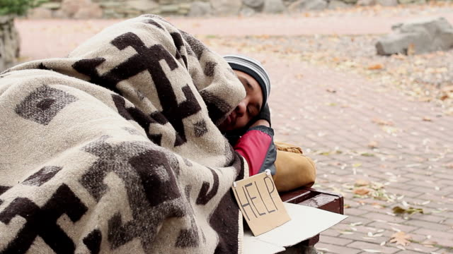 Thoughtful homeless man lying on bench in park with help sign. Begging, poverty video