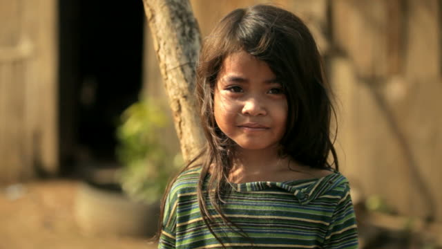 Thoughtful little girl in Cambodia Face of a cute little girl facing the camera, Beautiful light with wind in her hair. Age 5. Taken in Cambodia, Asia, poverty stock videos & royalty-free footage