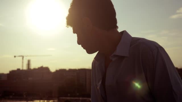 市夕日を考えて思いやりのある孤独な男喫煙電子タバコ - 屋根点の映像素材/bロール